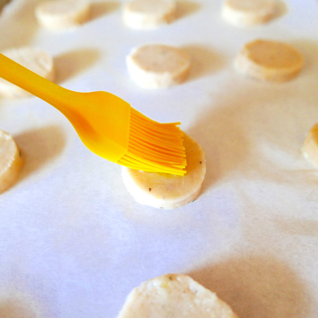 shortbread cookies on a baking sheet with a pastry brush brushing egg white on top