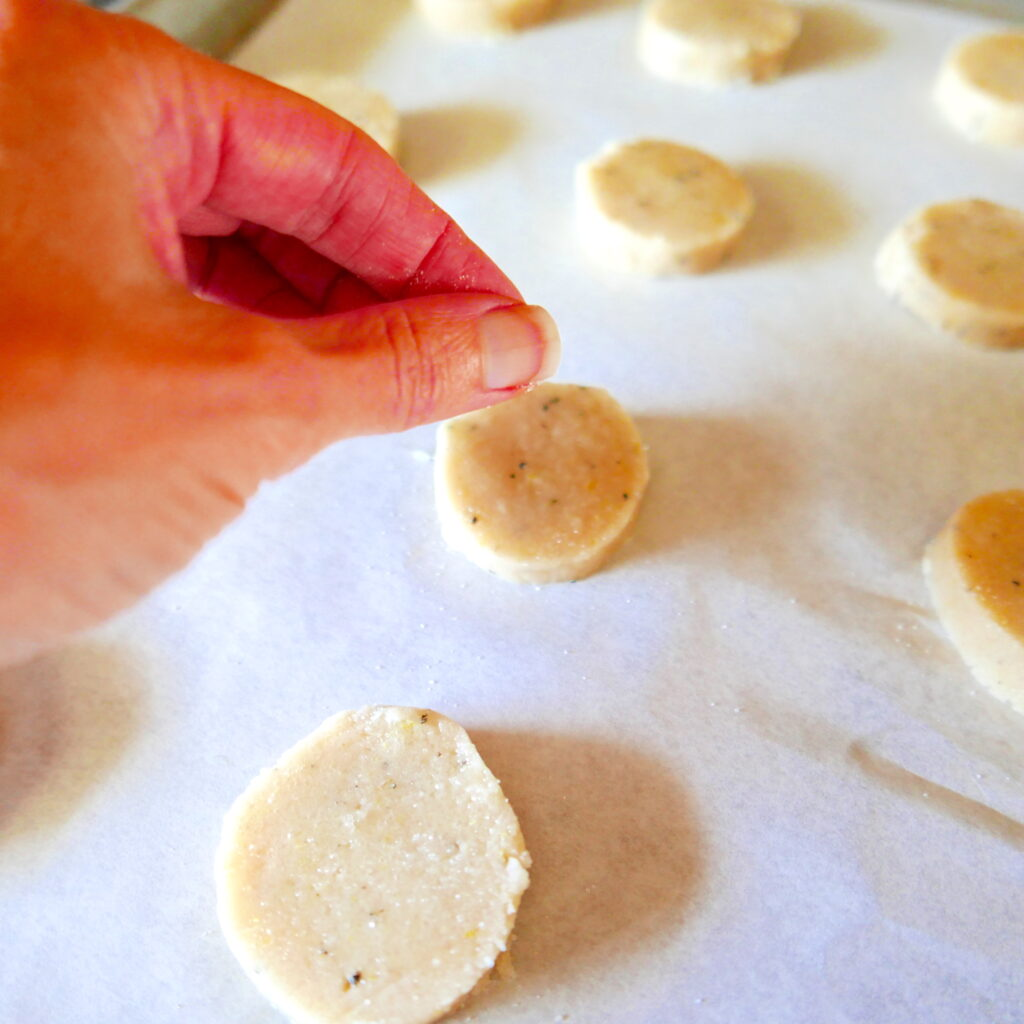 white hand sprinkling sugar onto shortbread cookies on a baking sheet