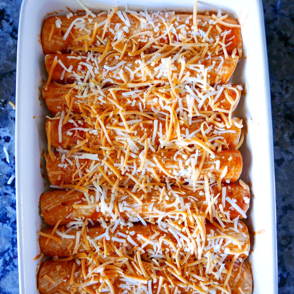 chipotle chicken enchiladas arranged in baking dish and covered with cheddar cheese
