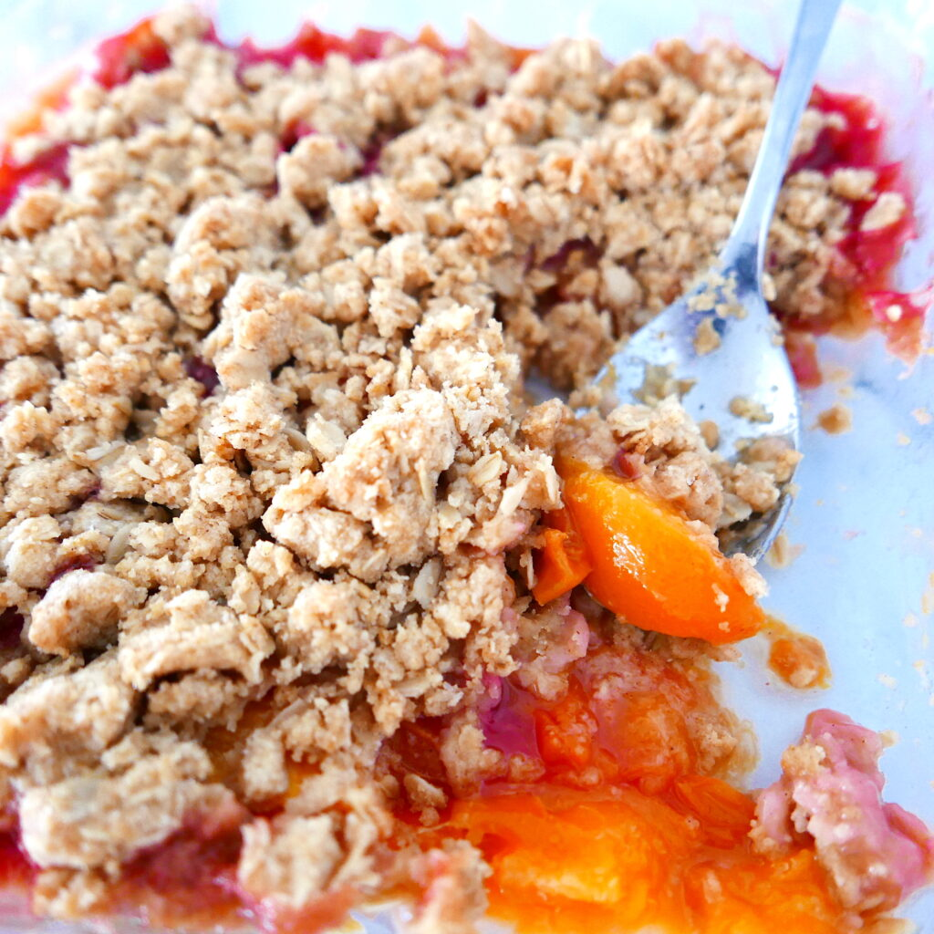 peach crisp in a baking dish with a spoon digging into crisp