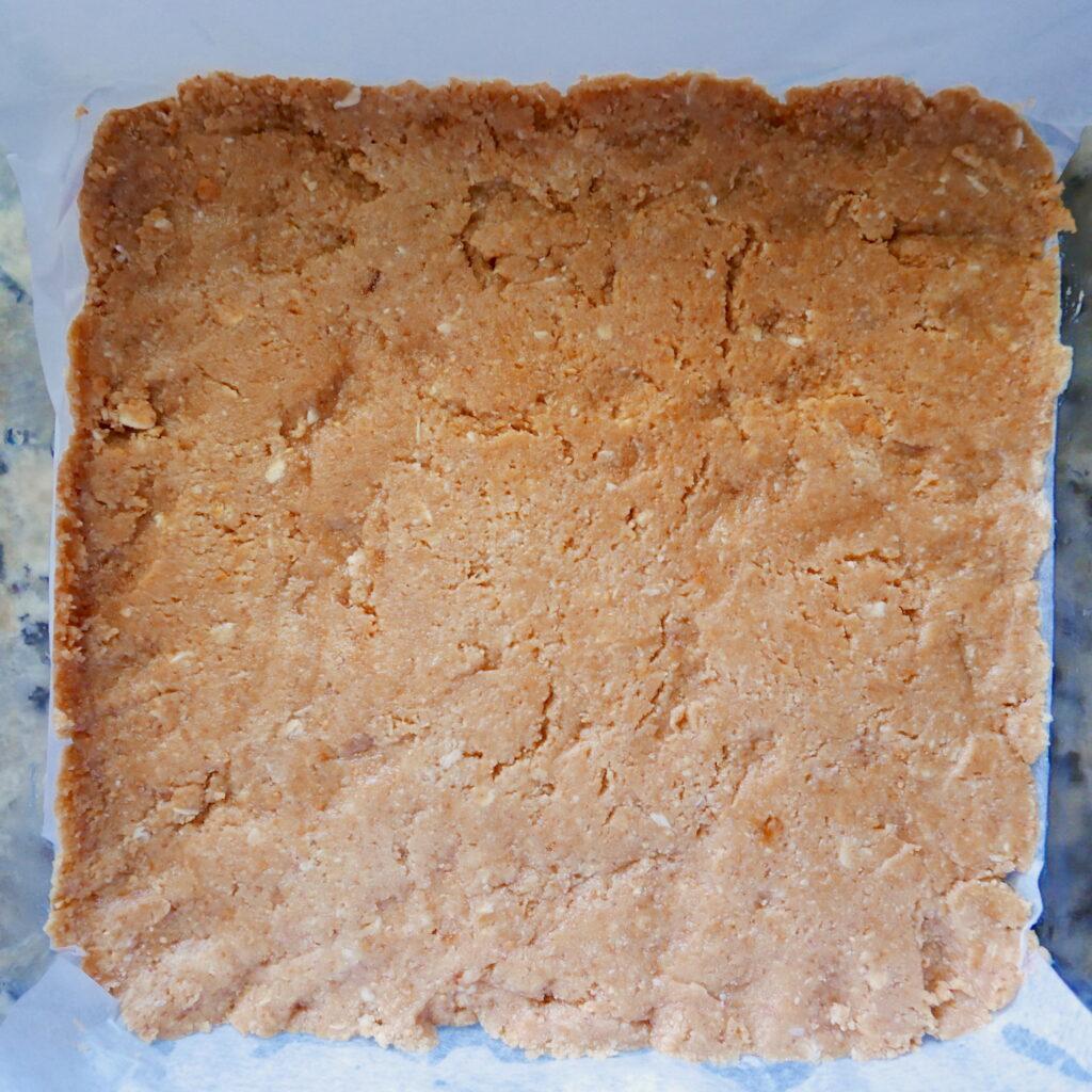 graham cracker cookie base in glass pan