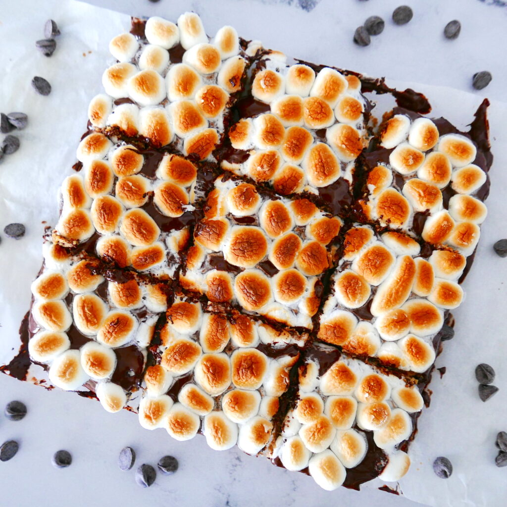 toasted marshmallow and chocolate bars cut into nine pieces on white counter with chocolate chips scattered around