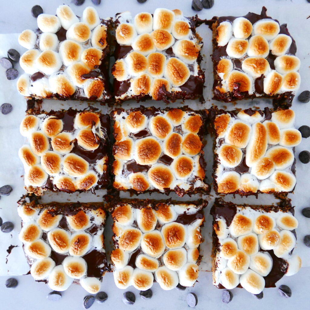 nine healthy smores bars arranged in a grid pattern with chocolate chips scattered around