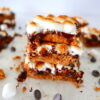 stack of three smores bars with more bars in the background and chocolate chips scattered around