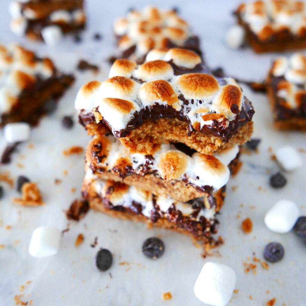 stack of three healthy smores bars with a bite taken out of the top one with chocolate chips and marshmallows scattered around