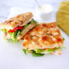 two chicken avocado focaccia sandwiches leaning against each other with a small cup of mayo in the background