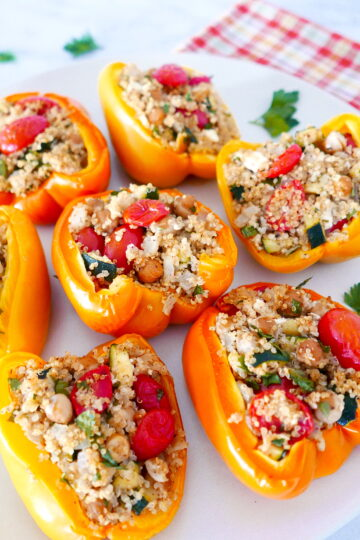 mediterranean stuffed peppers arranged on a white plate with cilantro scattered around plate
