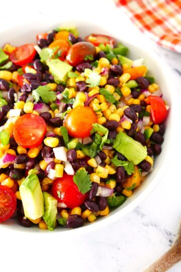 corn avocado black bean salsa in a white bowl with wooden spoon next to it on marble counter