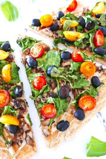vegan flatbread pizza with lots of veggies arranged on a marble table