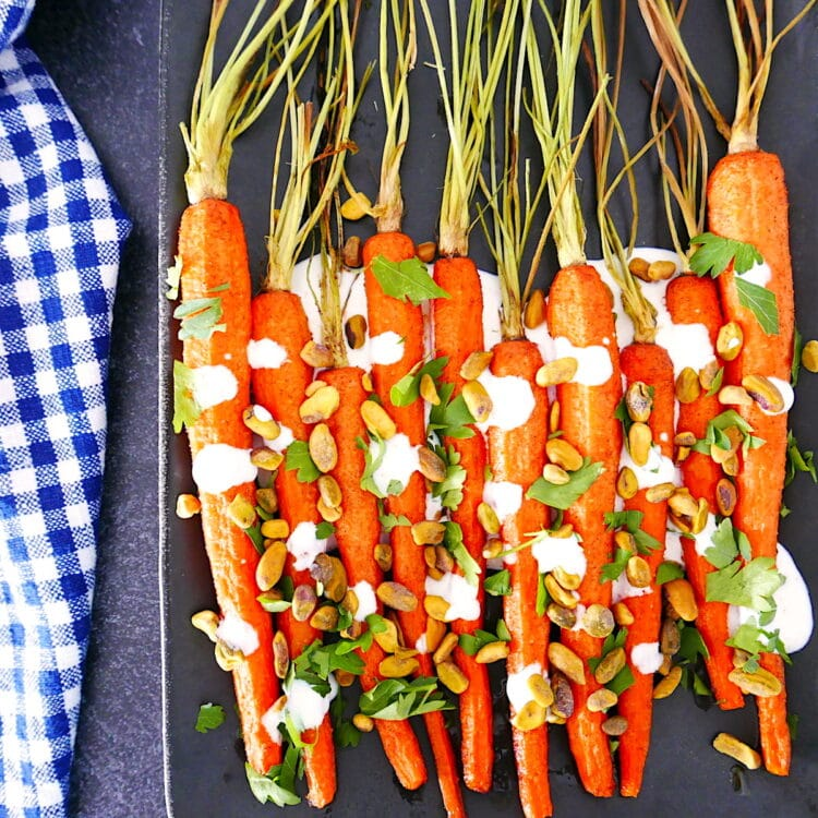 cumin roasted carrots with yogurt sauce on a grey platter with a blue and white napkin next to it