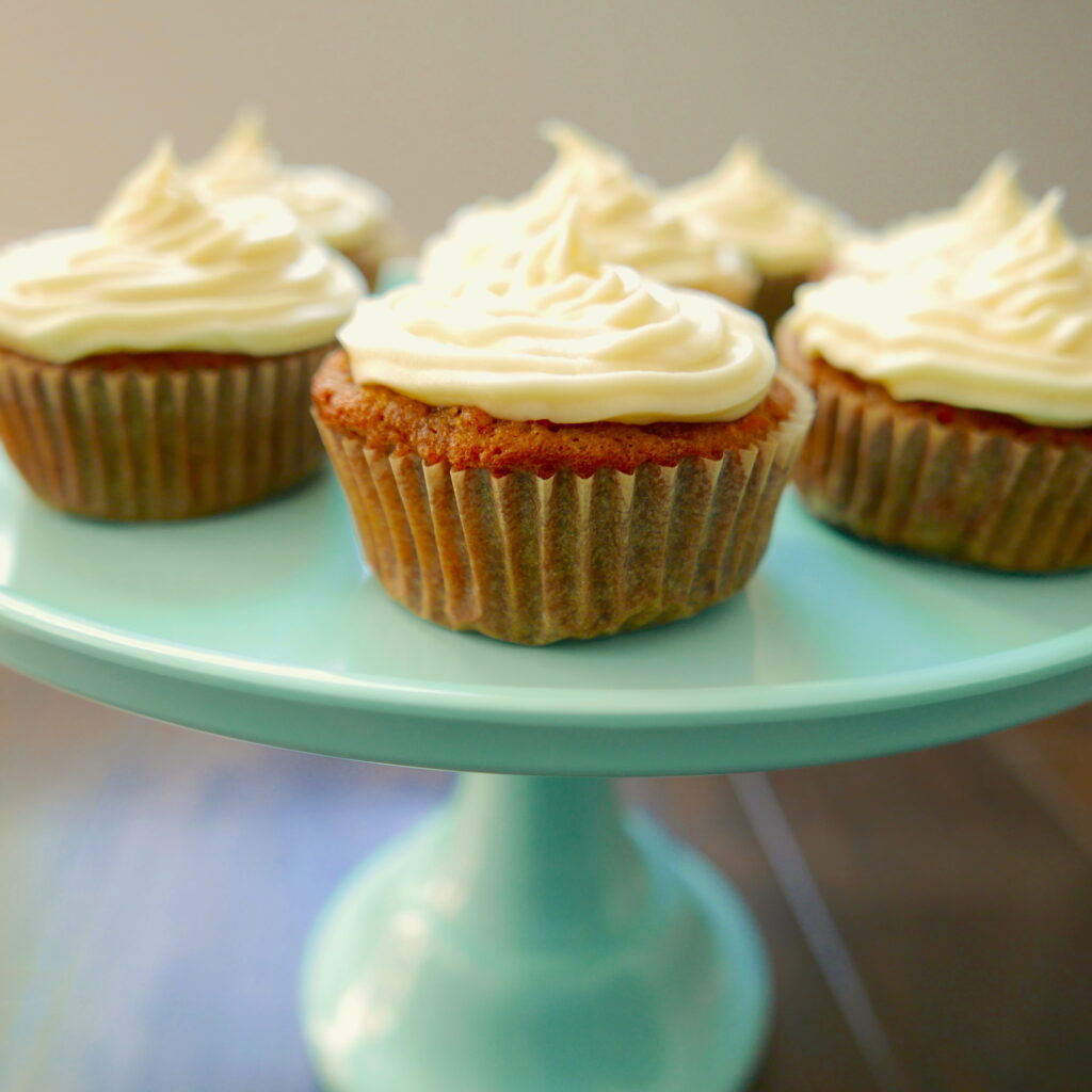 carrot cake cupcakes with cream cheese frosting on an aqua cake stand