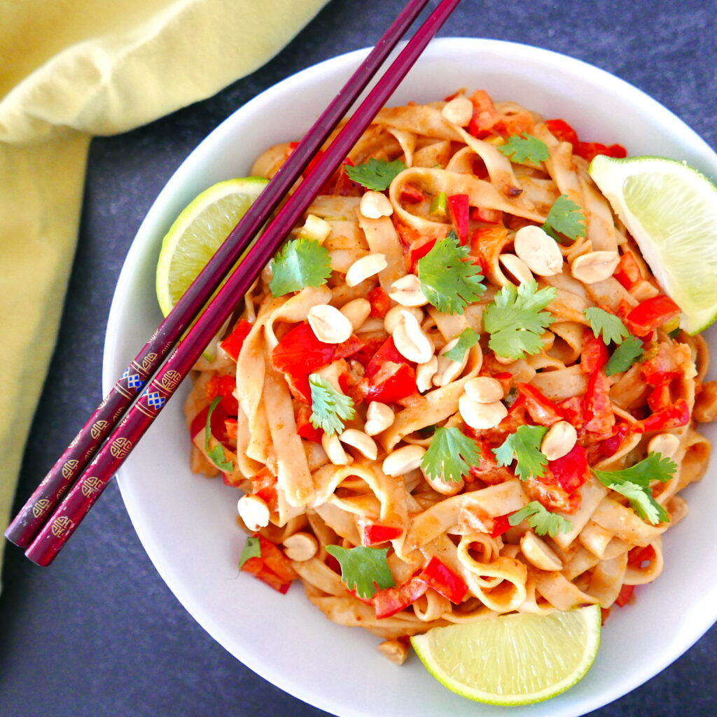 vegan peanut noodles in a white bowl with chopsticks and lime wedges