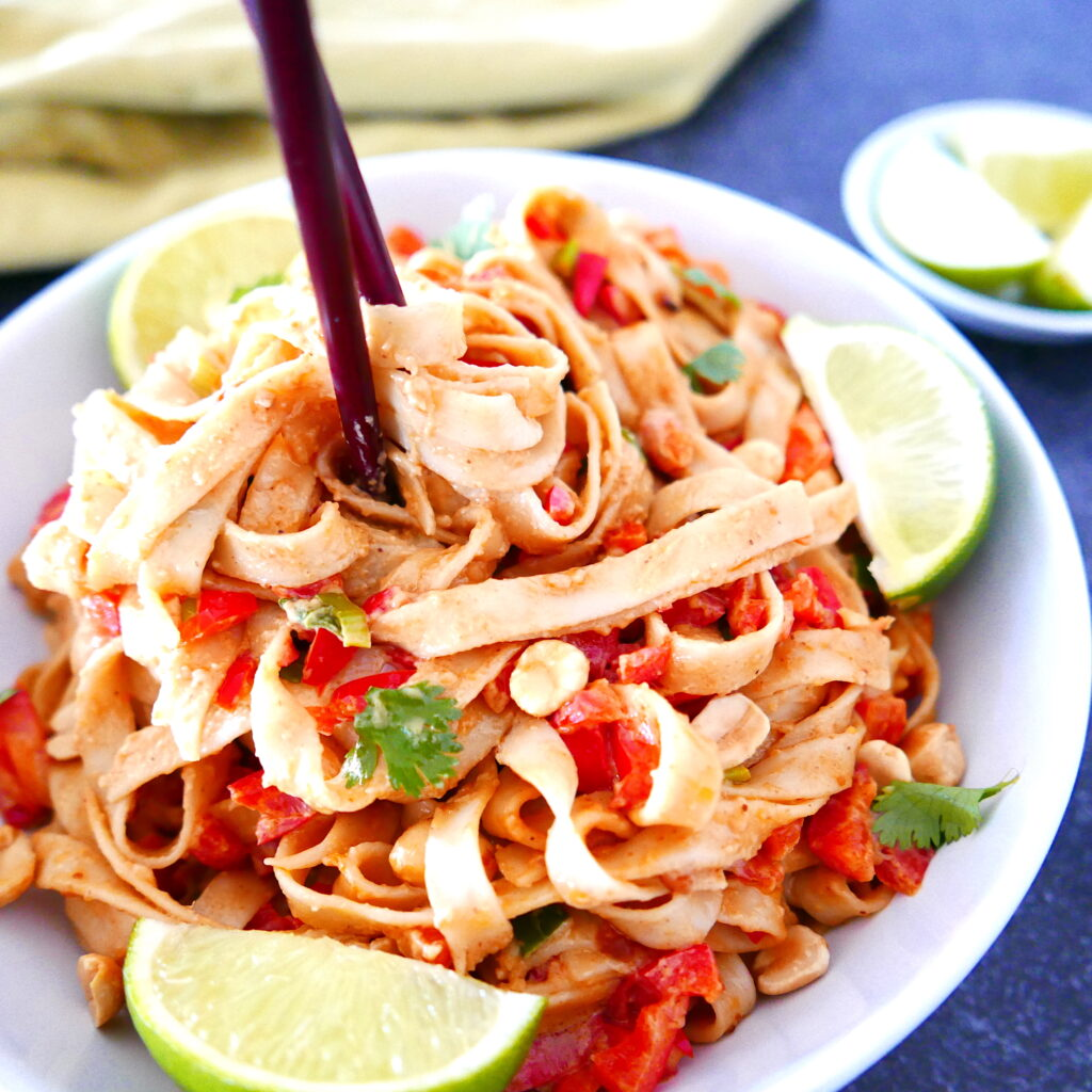 two chopsticks scooping up noodles with cilantro and lime wedges in a white bowl