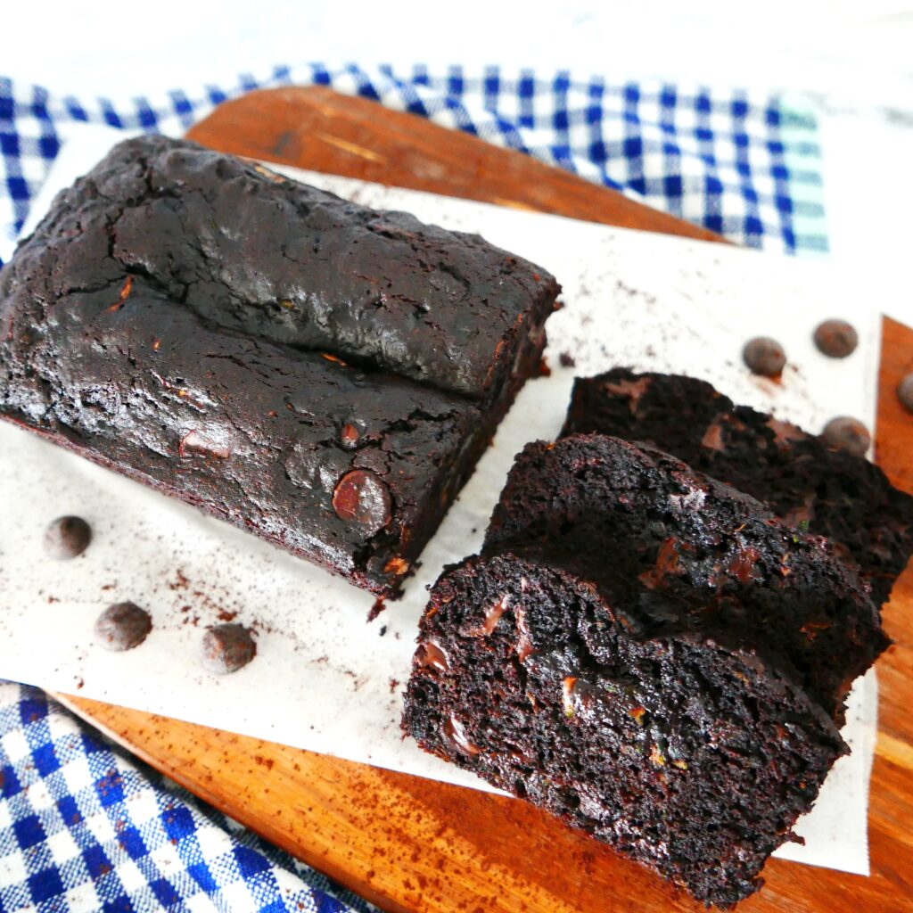 chocolate zucchini bread cut into slices on parchment paper with chocolate chips scattered nearby