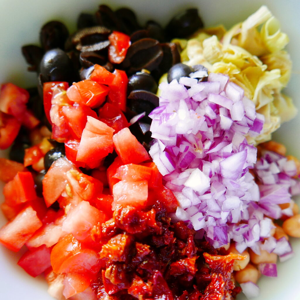 chopped red onion, tomatoes, artichokes, black olives, and chickpeas in a mixing bowl