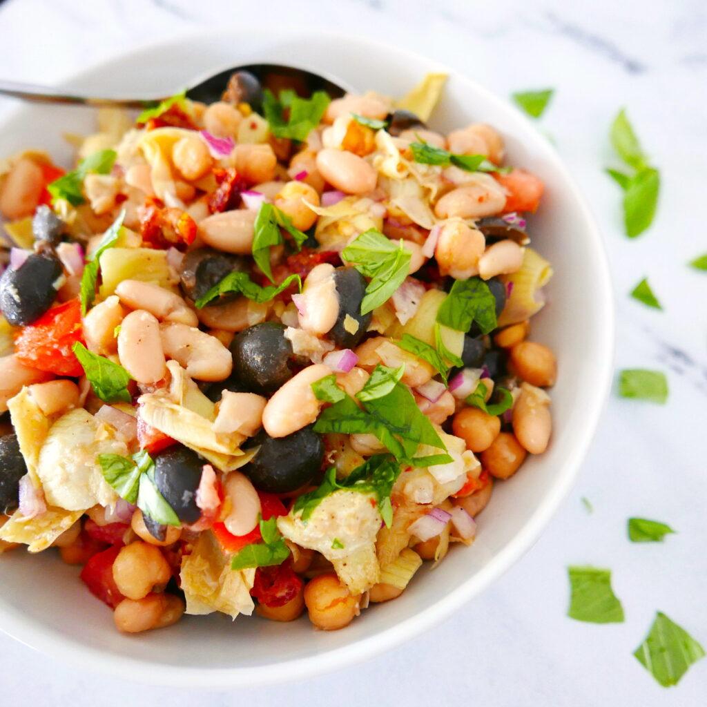 bean salad with basil in a white bowl with spoon in bowl and torn basil scattered near bowl
