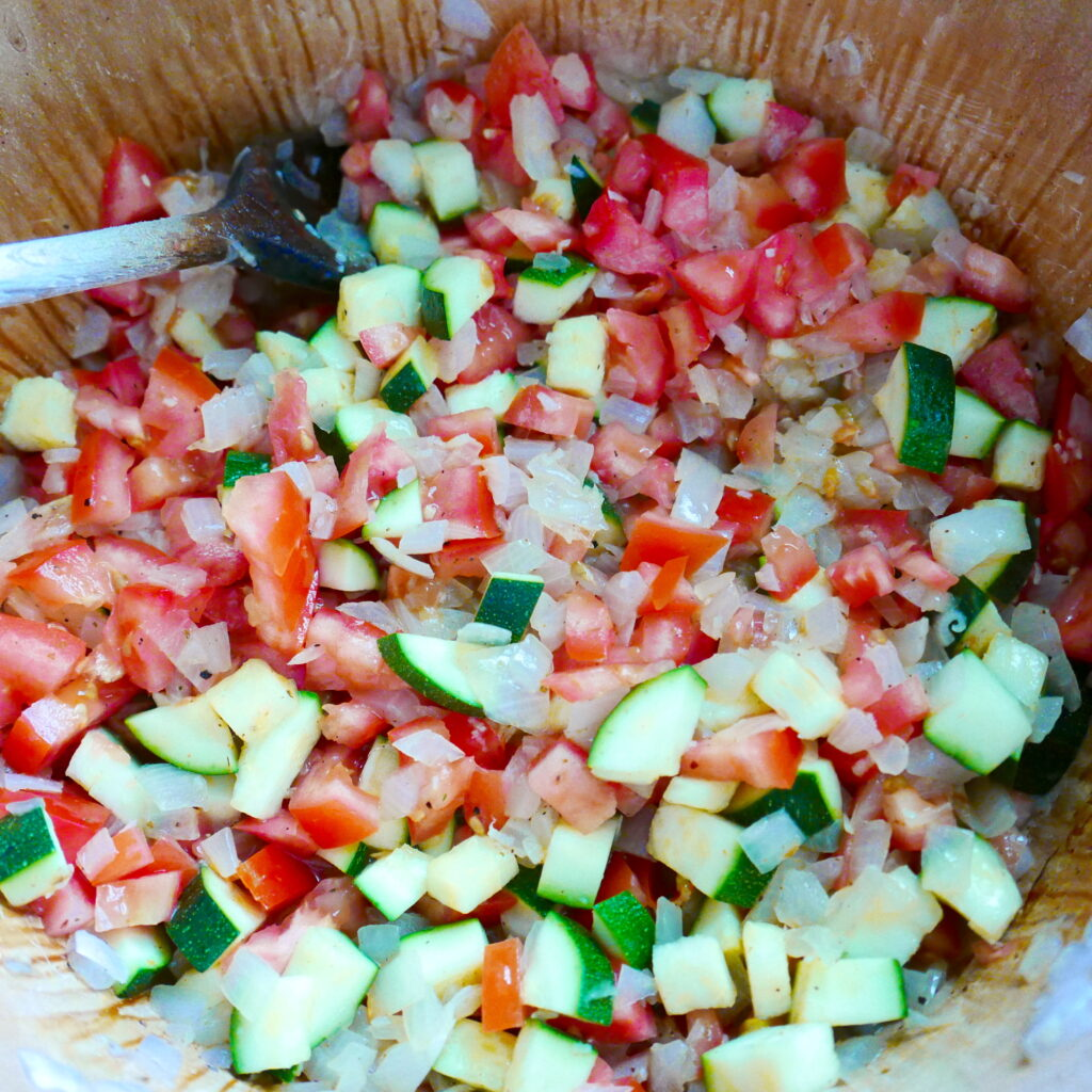 zucchini, tomato, and onion cooking in a dutch oven with wooden spoon