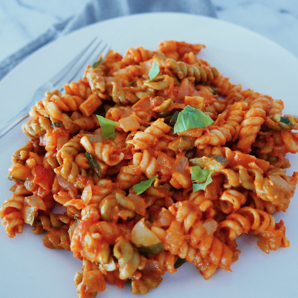 tomato basil pasta with zucchini on a white plate with fork