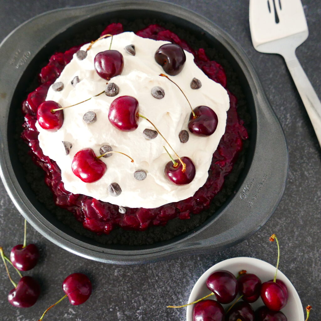 black forest cherry pie with cup of cherries in the foreground and pie server in the background