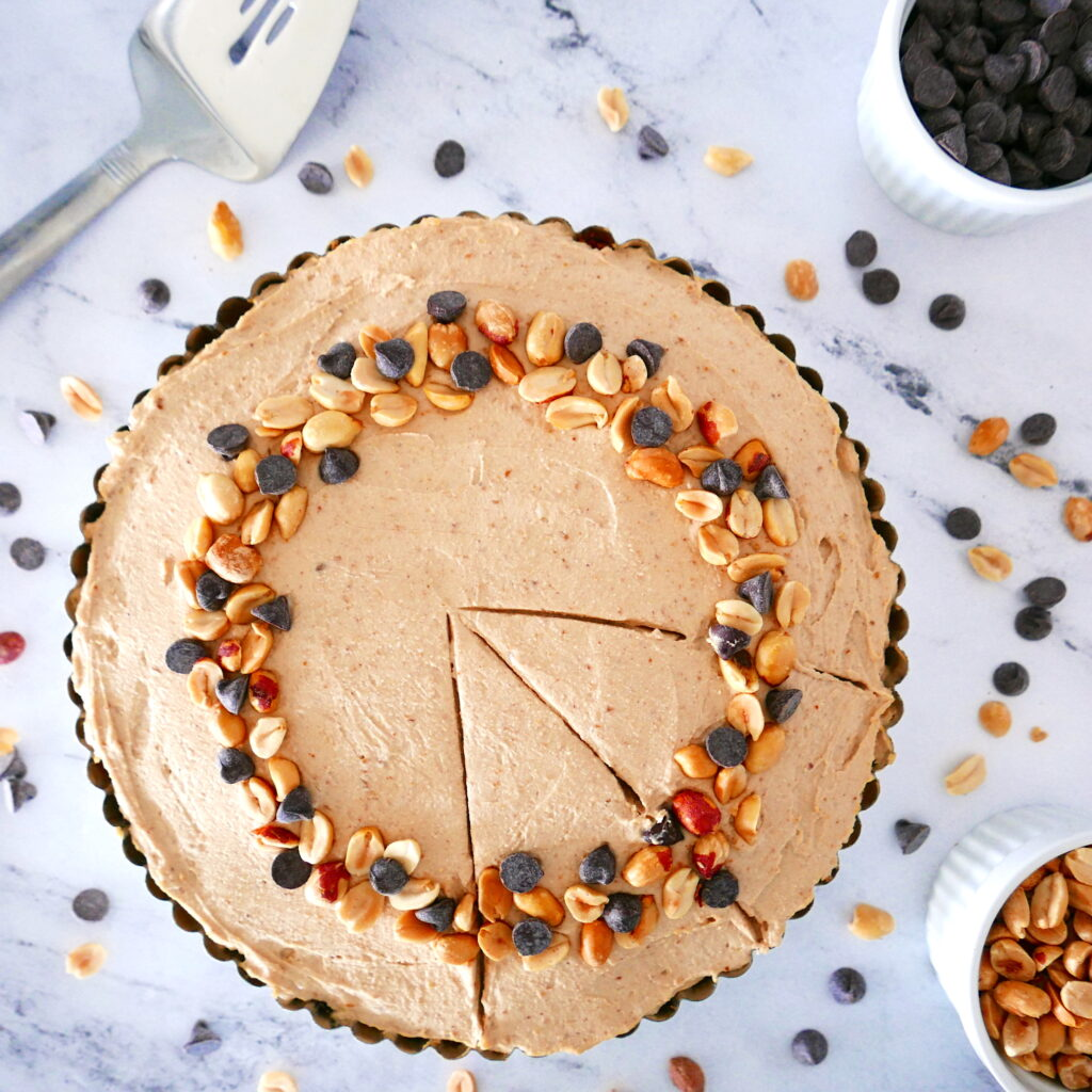 vegan peanut butter pie topped with chocolate chips and peanuts and lots of nuts and chips scattered around pie with pie server in the background