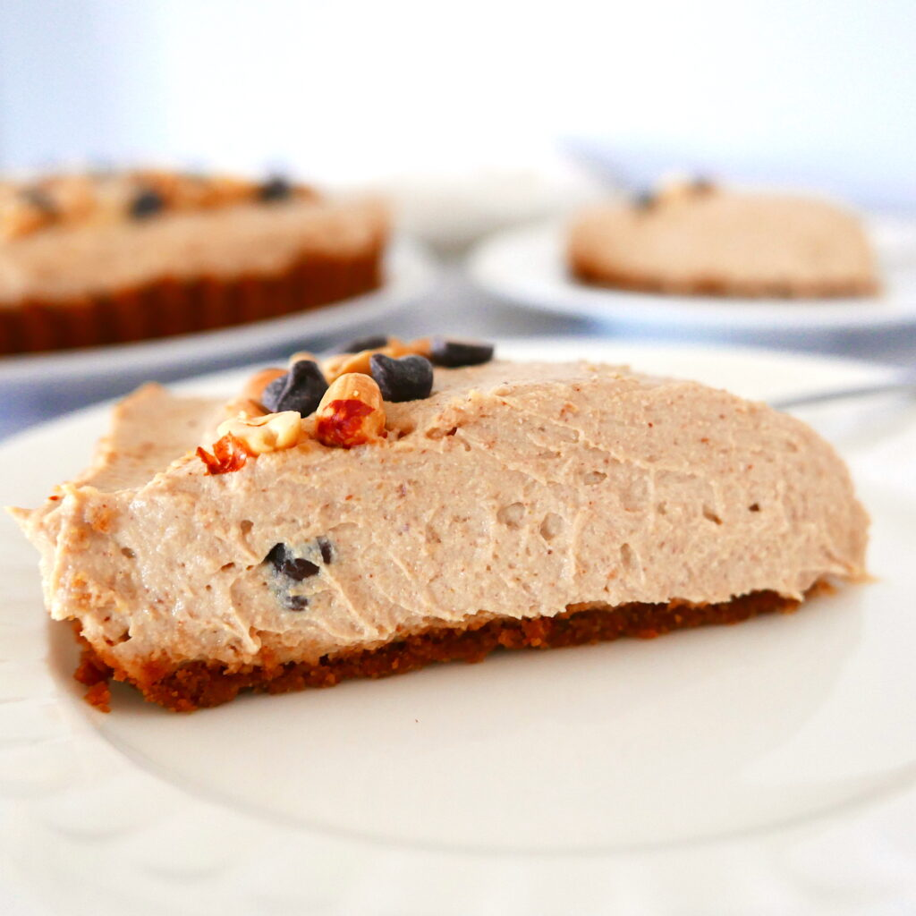 close up of cut piece of peanut butter pie on a white plate with more pieces in the background