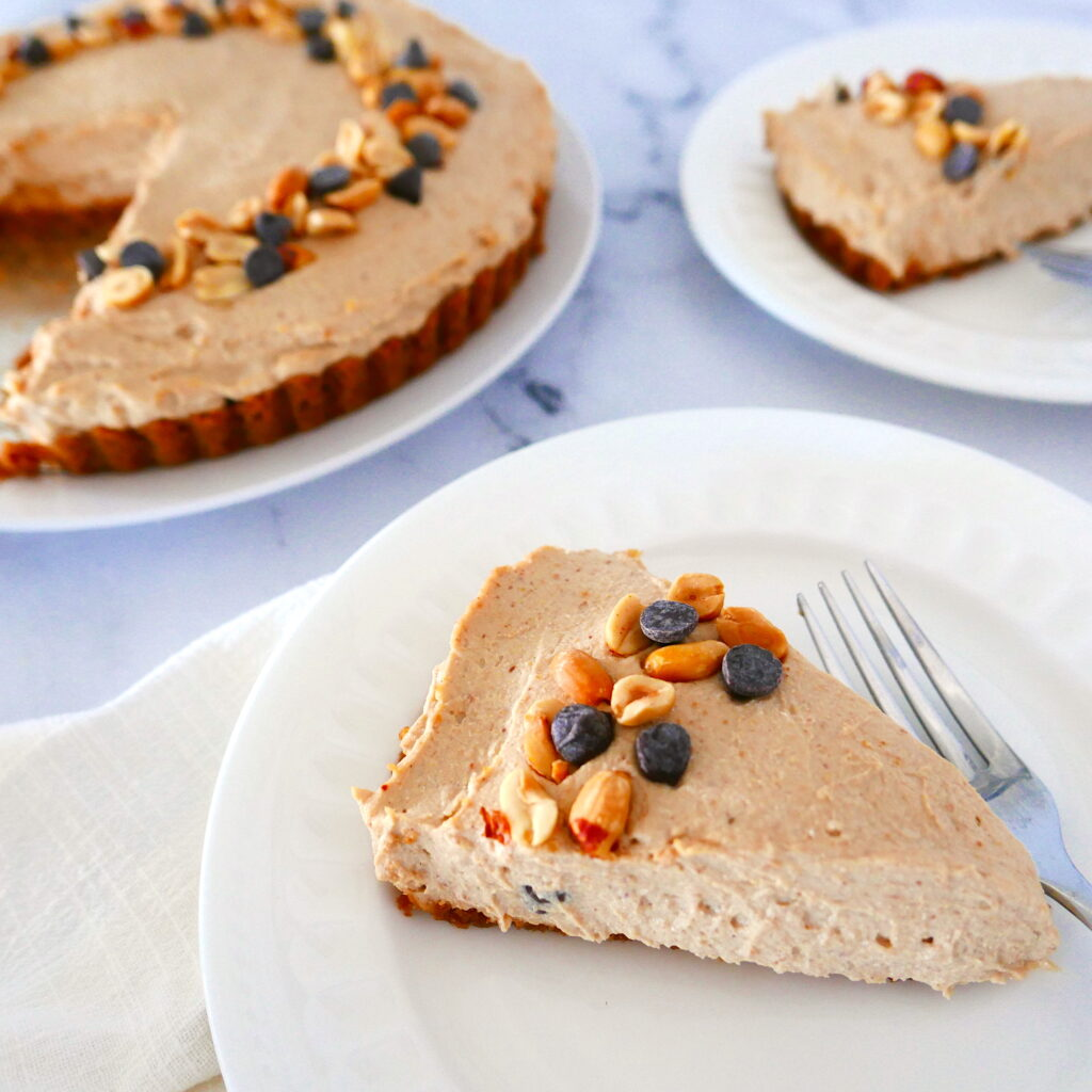 vegan peanut butter pie with two pieces in the foreground on white plates
