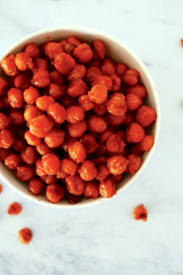 bbq roasted chickpeas in a small bowl with chickpeas scattered around bowl