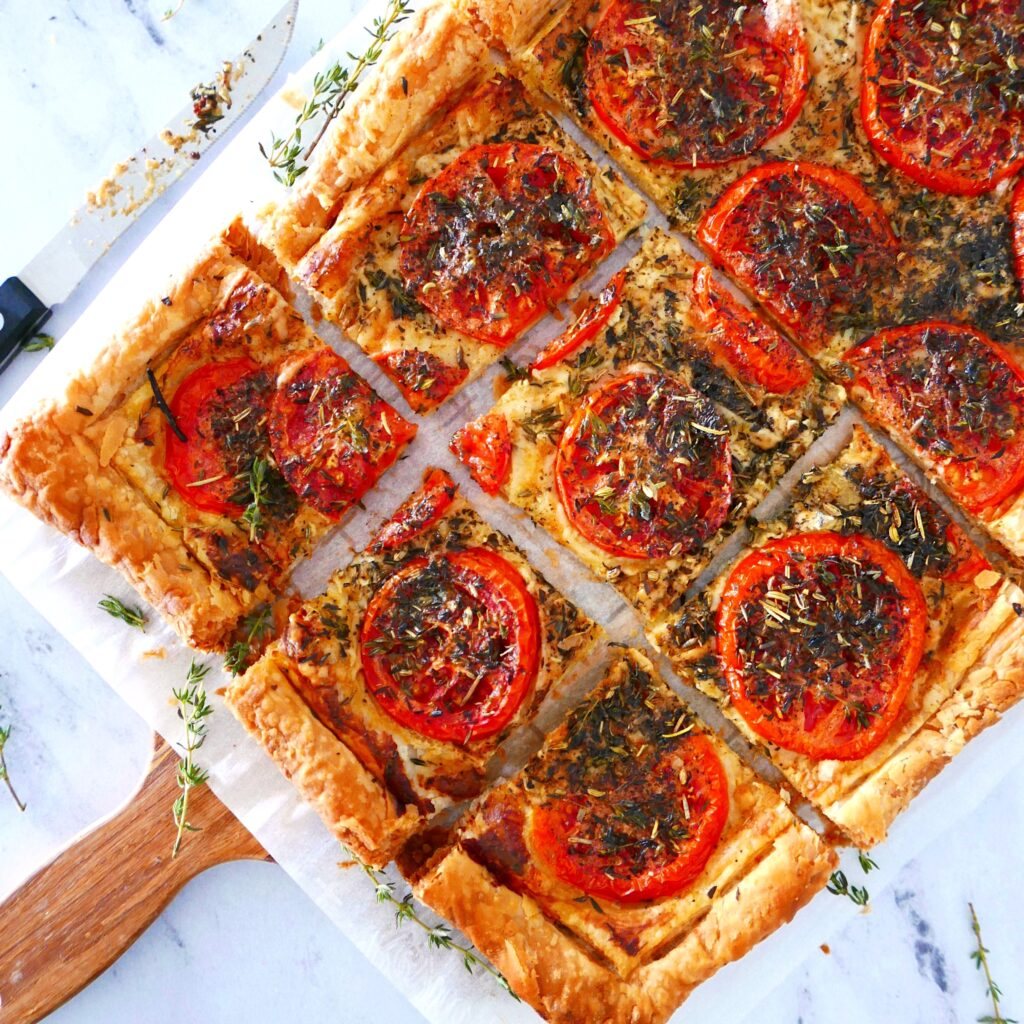 french tomato tart cut into squares and arranged on a wooden cutting board