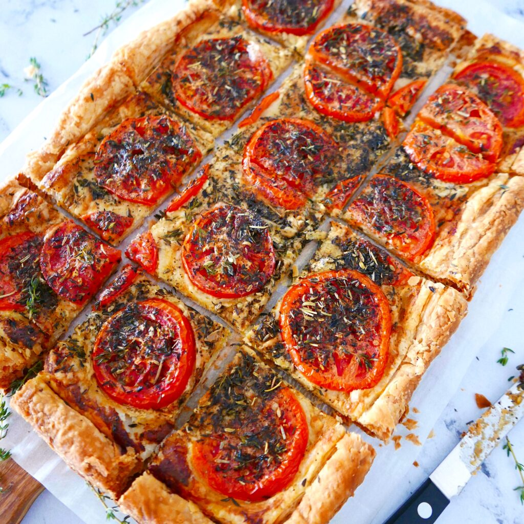 french tomato tart cut into squares on a white counter with knife next to tart