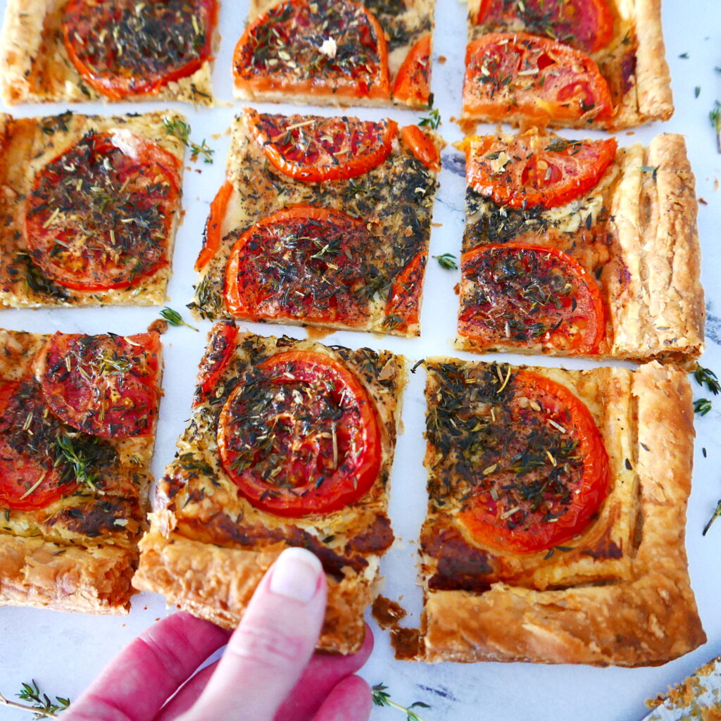 french tomato tart cut into squares with a white hand picking up one piece of tart