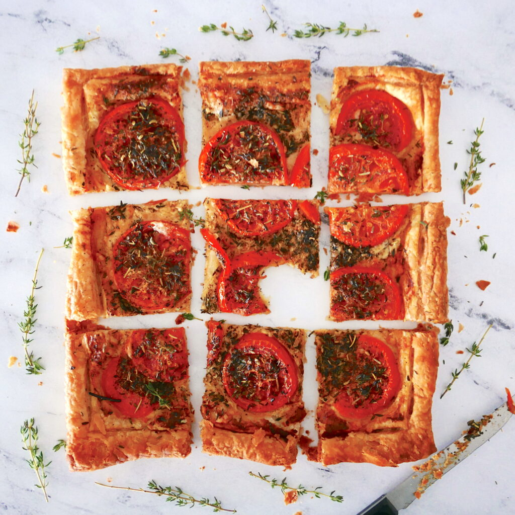 tomato pastry arranged in a grid with center piece missing a bite