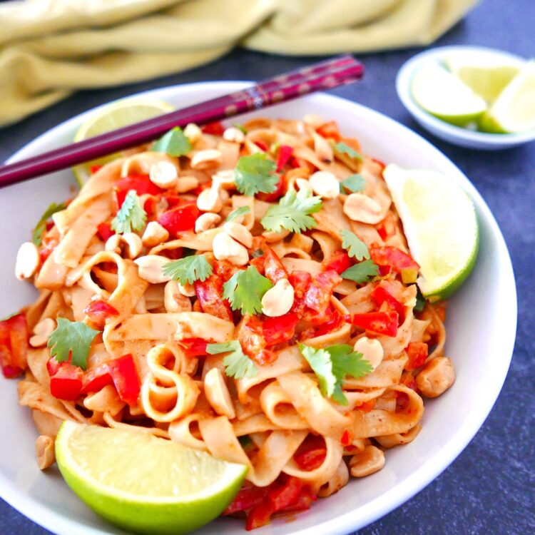 vegan peanut noodles on a white plate with chopsticks and two lime wedges