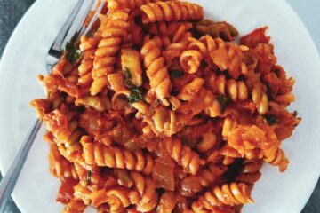 pasta with tomato mascarpone sauce on a white plate with fork