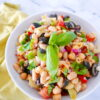 tuscan bean salad in a white bowl garnished with basil and a green napkin next to bowl