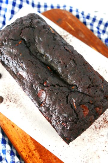 death by chocolate zucchini bread on a wooden cutting board on top of a plaid napkin