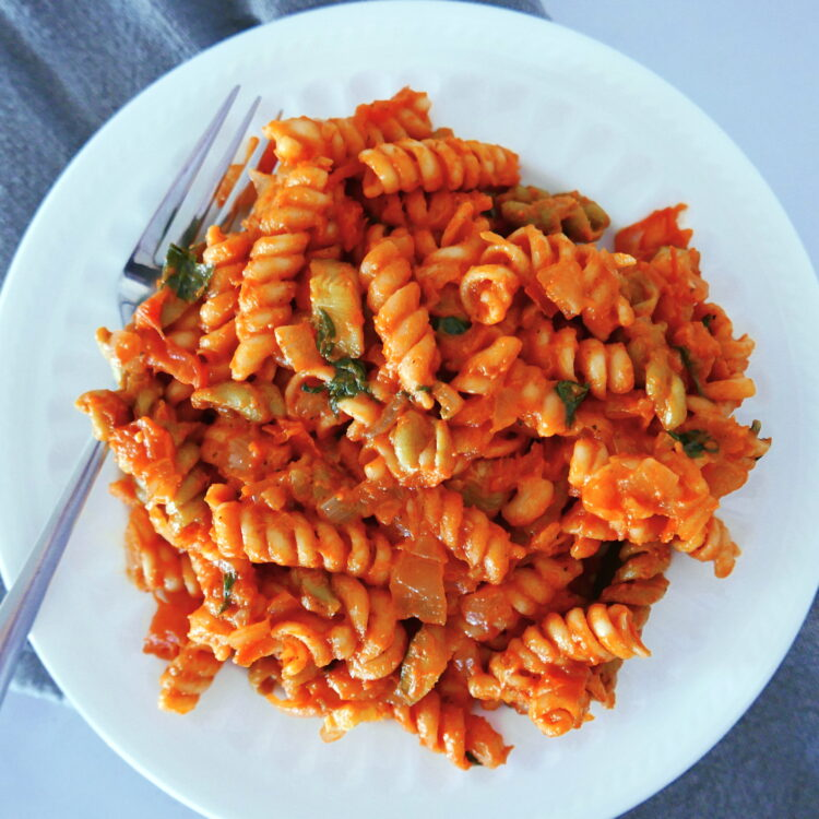 pasta with tomato mascarpone sauce on a white plate with fork and gray napkin