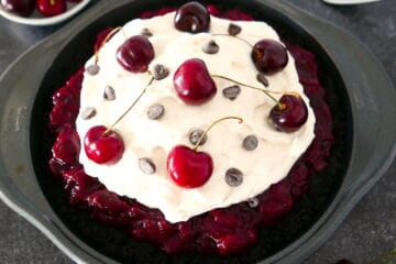 black forest cherry pie with two forks in the background and a cup of cherries nearby