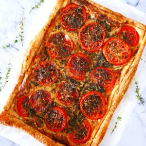 french tomato tart resting on a white counter with fresh thyme scattered around