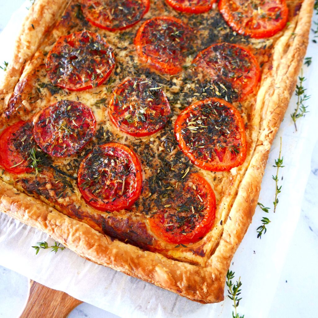 corner of french tomato tart with thyme scattered around