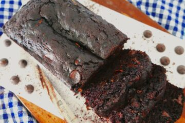 death by chocolate zucchini bread sliced on a wooden cutting board with a checkered napkin underneath