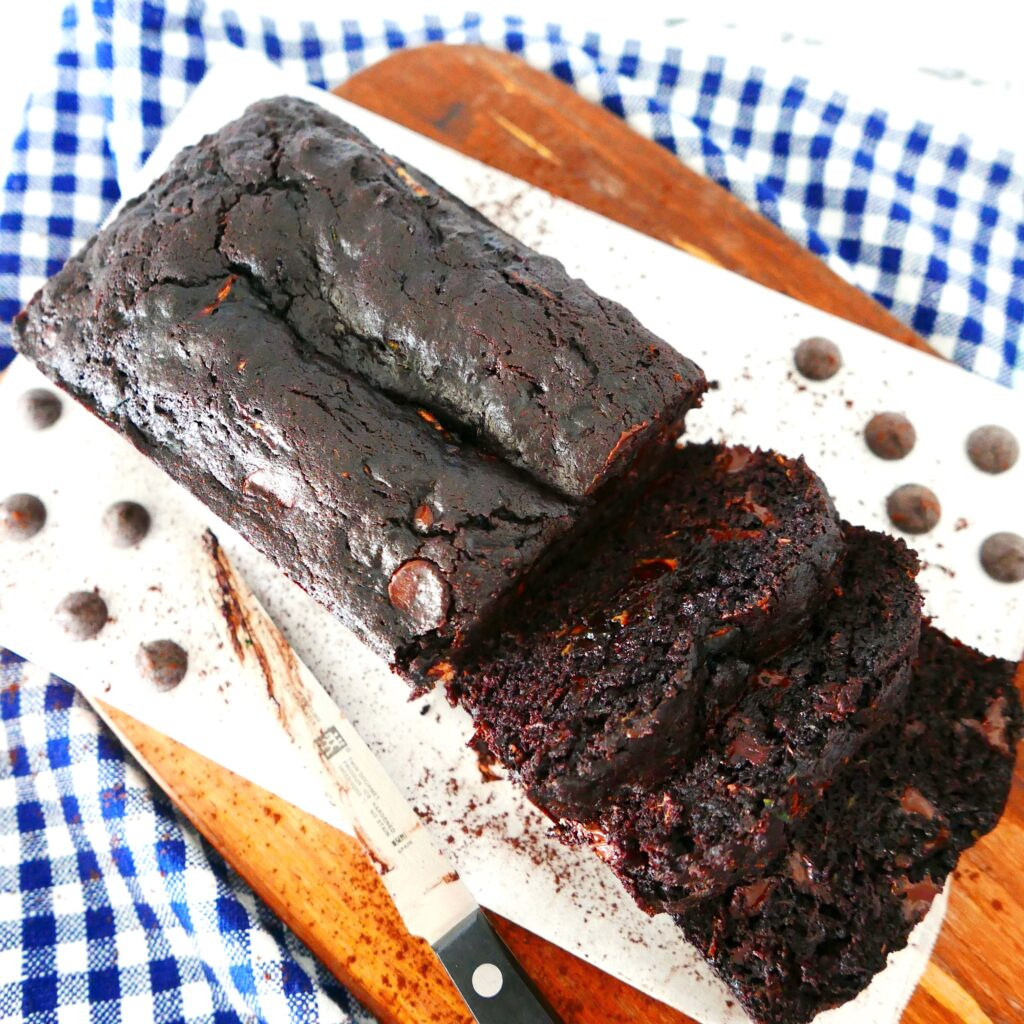 death by chocolate zucchini bread sliced on a wooden cutting board with a knife nearby on top of a plaid napkin