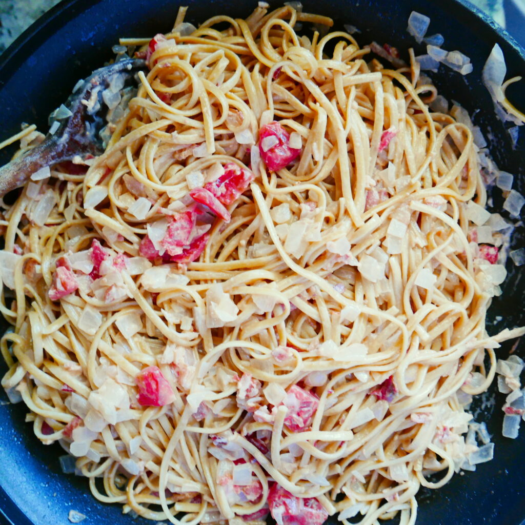 pasta with tomatoes and onion cooking in a pan