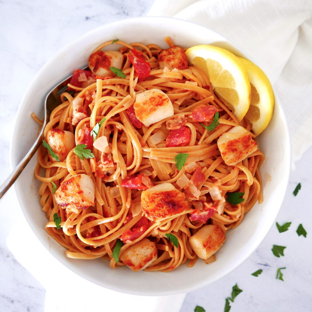pasta with scallops and bacon in a white bowl with lemon wedges and a fork