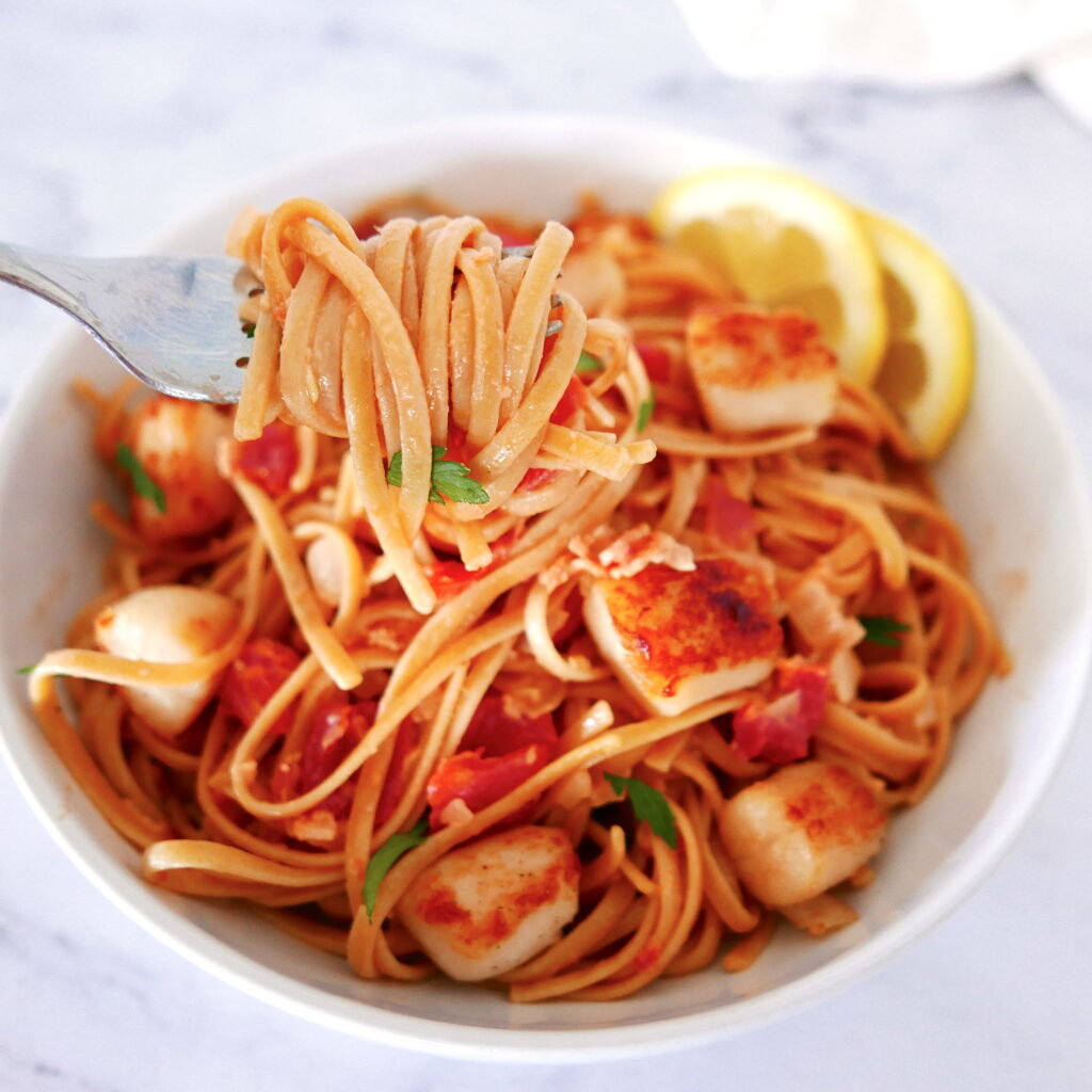 fork lifting up pasta with scallops and bacon out of a white bowl