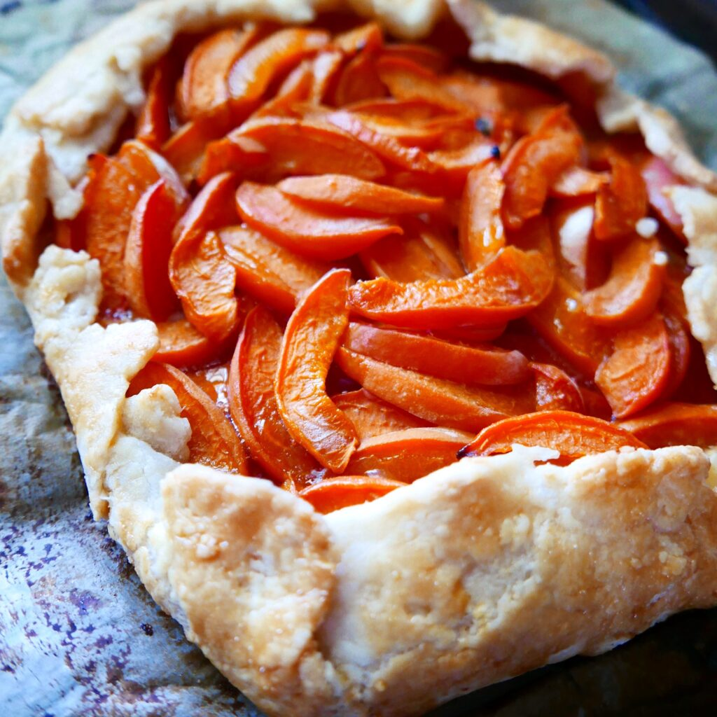 the corner of a stone fruit galette resting on a pan