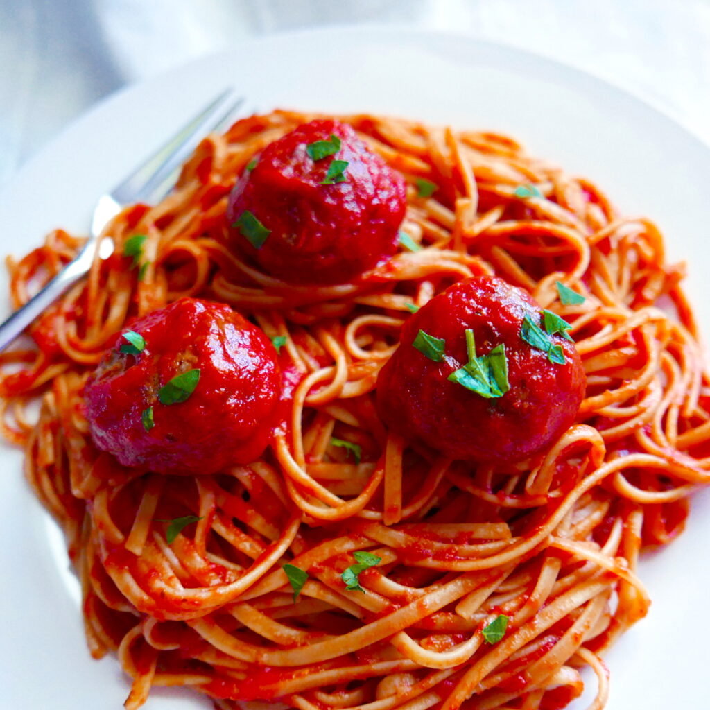 impossible meatballs in tomato sauce with spaghetti noodles on a white plate with fork