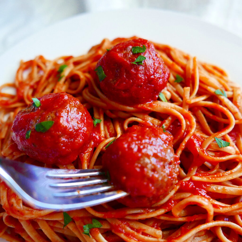 fork picking up meatball off of plate with spaghetti and impossible meatballs