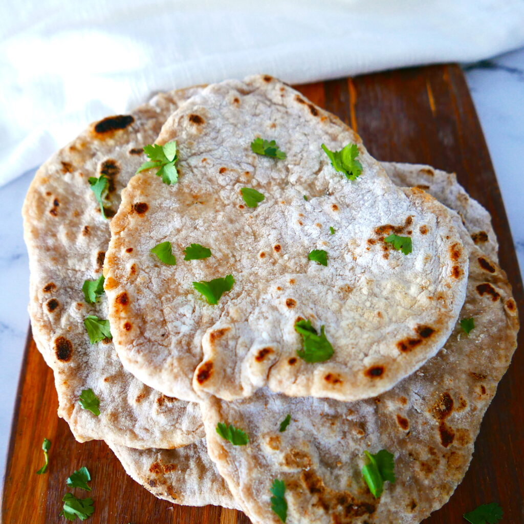 five pieces of sourdough naan arranged on a wooden board and garnished with cilantro