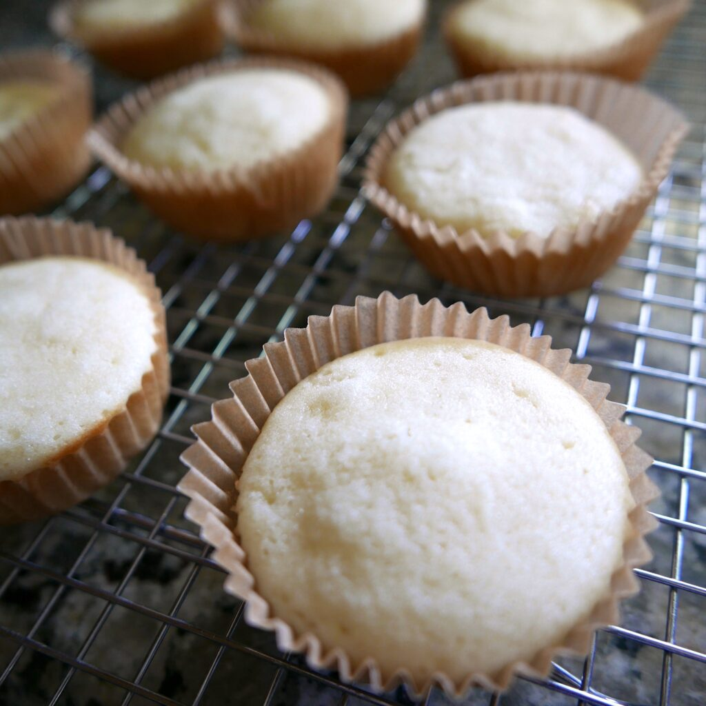 almond cupcakes cooling on a wire rack