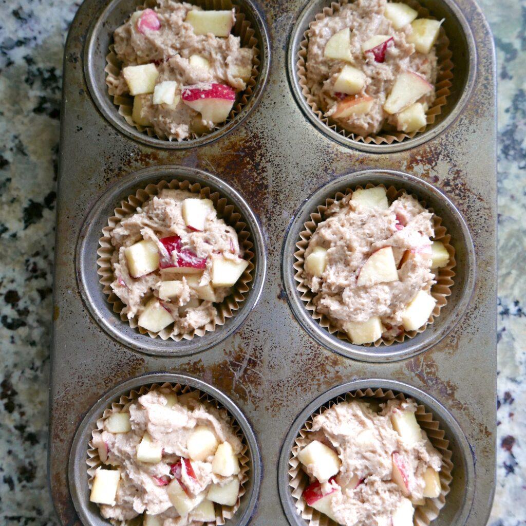 apple muffin batter in a muffin tin